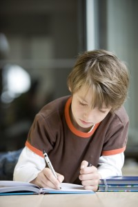 boy writing in book during tutoring session